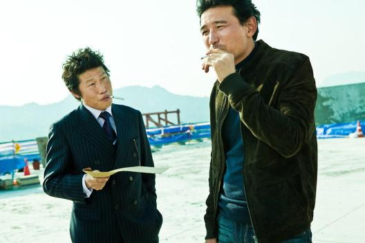 Detective Choi (right) enlists the help of Jang to find a scapegoat