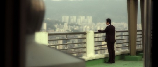 The man stares at the vast cityscape in which he inhabits