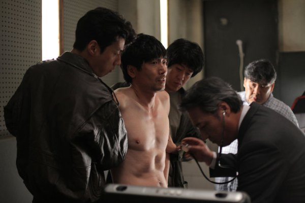 Jong-tae is stripped naked and humiliated as preparations for torture begin