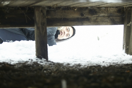 Screenwriter Sang-jin inspects his cabin the wintry countryside