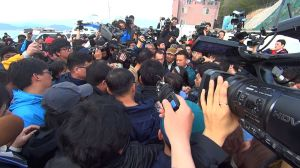 Footage of the media frenzy at the site convey the chaos and demand for answers